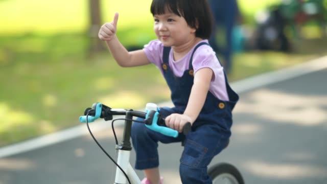 Asiatische kleine Mädchen fahren Fahrrad, gutes Schild, Daumen hoch