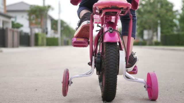 vídeos y material grabado en eventos de stock de asiática niña montar en bicicleta en el jardín - montar