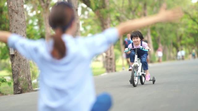 Asiatische kleine Mädchen fahren Fahrrad mit Mutter im Garten, Arme ausgestreckt