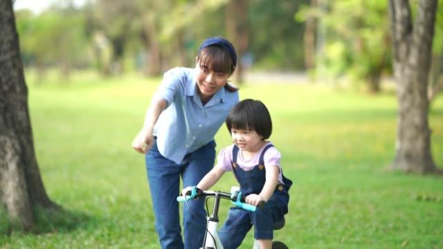 Asiatisches Mädchen fährt Fahrrad mit junger Lehrerin im Garten