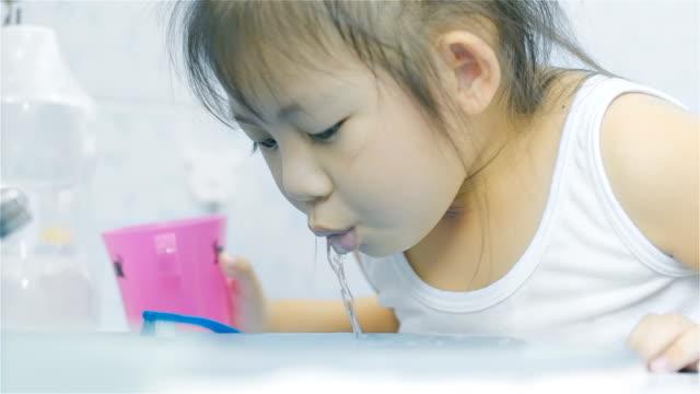 vídeos de stock e filmes b-roll de asian little girl rinse her mouth after brushing her teeth in bathroom - escova de dentes