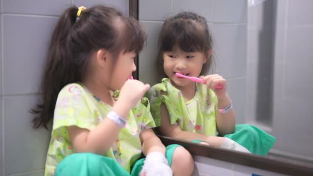 asian little girl sick in the hospital brushing her teeth in bathroom - dental health stock videos & royalty-free footage