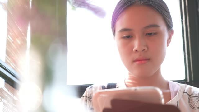 vidéos et rushes de petite fille asiatique utilisant la tablette - message sms