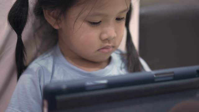 bambina asiatica che guarda e gioca a tablet digitale - organizzatore elettronico video stock e b–roll