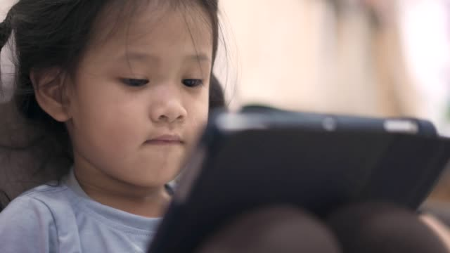asian little girl watching and playing digital tablet - one baby girl only stock videos & royalty-free footage