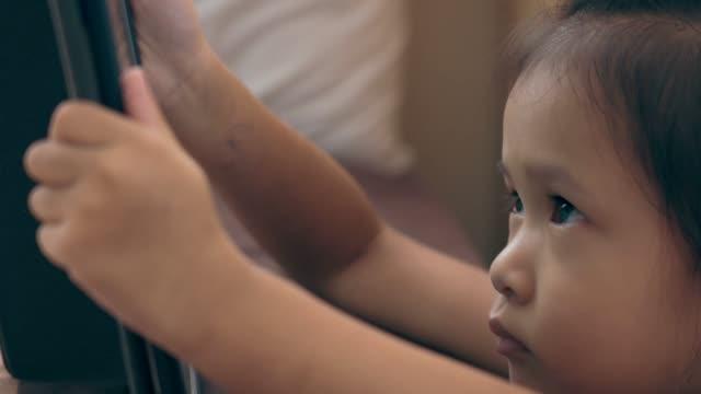 vídeos de stock, filmes e b-roll de menina asiática que presta atenção e que joga a tabuleta digital - agenda eletrônica