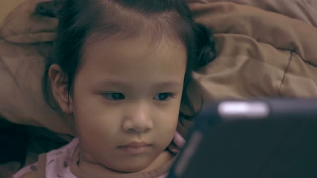 asian little girl watching and playing digital tablet - electronic organiser stock videos & royalty-free footage