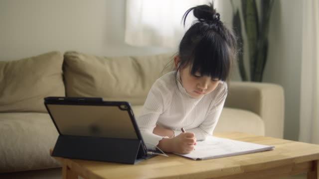 アジアの小さな女の子は、ウェブカメラで呼び出すヘッドセット会議を着用 - インストラクター点の映像素材/bロール