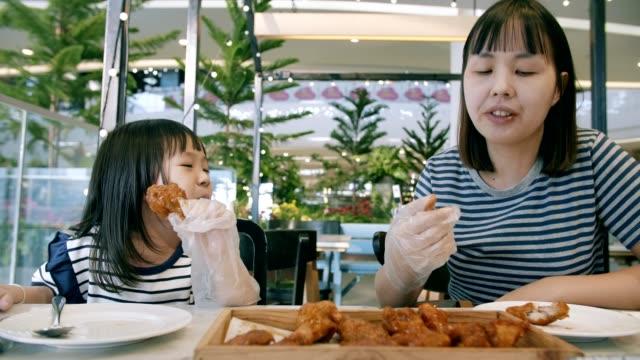 vídeos y material grabado en eventos de stock de niña de asia (4-5 años) con su madre en la hora del desayuno - pollo frito