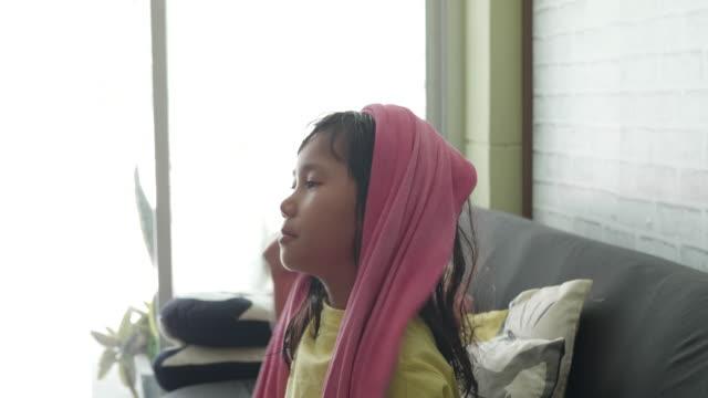 Aziatisch meisje met natte haren bedekt met een handdoek, dagelijkse Lifestyle Videography.