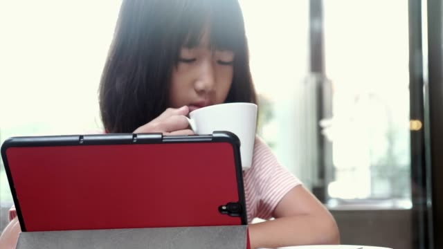 asian little girls playing tablet, drinking hot milk at table in cafeteria. - breakfast stock videos & royalty-free footage