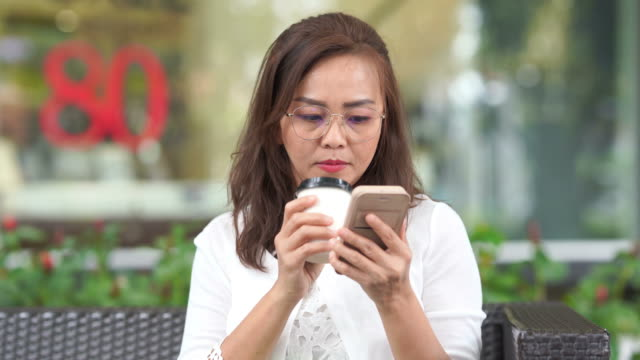 asian luxury mature woman using smartphone and drink hot coffee from take away cup - internet dating stock videos and b-roll footage