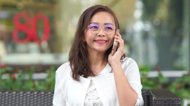 Aziatische luxe volwassen vrouw met behulp van smartphone op terras