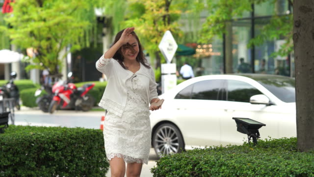 asian luxury mature woman using smartphone at  while crossing on street - beckoning stock videos & royalty-free footage