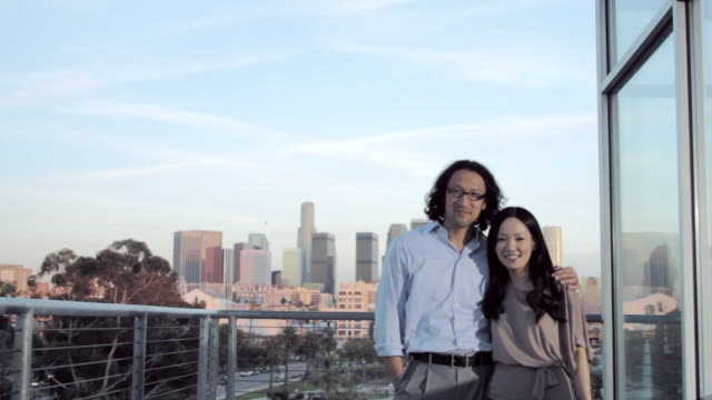 MS Asian male and female looking towards camera at balcony of corporate building  / Los Angeles, CA, United States