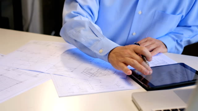 vídeos de stock e filmes b-roll de asian male architect or engineer studying plans and using tablet in office at desk with plans - engenharia