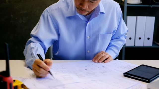 vídeos y material grabado en eventos de stock de arquitecto hombre asiático o planes de estudio de ingeniero y uso de tableta en oficina en el escritorio con planes - estudio de diseño