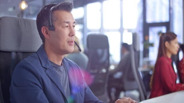 vidéos et rushes de ds asiatique homme agent de centre d'appels gérant des appels dans un bureau moderne - opérateur téléphonique