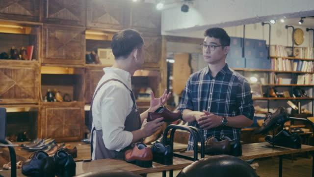 vídeos y material grabado en eventos de stock de clientes masculinos asiáticos comprando zapatos en la zapatería (movimiento lento) - lugar de comercio