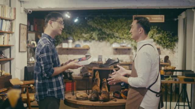 メンズウェアショップでネクタイを購入するアジアの男性顧客(スローモーション) - 百貨店点の映像素材/bロール