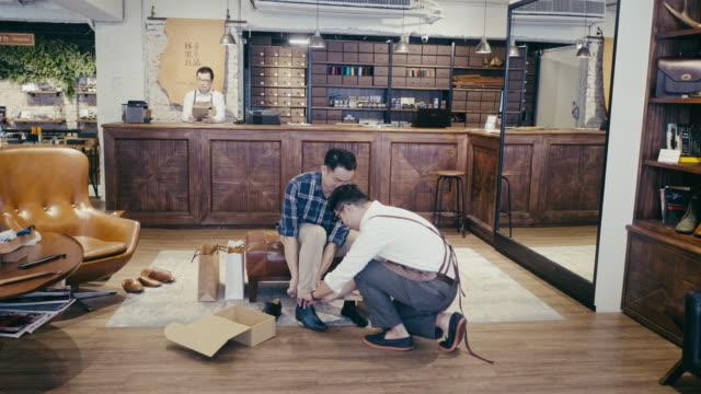 アジアの男性顧客は、靴屋で顧客サービスから助けを得る - 百貨店点の映像素材/bロール