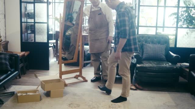 cliente asiatico maschio che prova le scarpe e guarda lo specchio - misurare video stock e b–roll