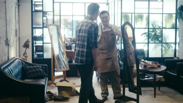 アジアの男性客が靴を試してみて、鏡を見て - 百貨店点の映像素材/bロール