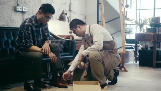 vídeos de stock e filmes b-roll de asian male customer trying on shoes at the shoe shop - cabine de loja