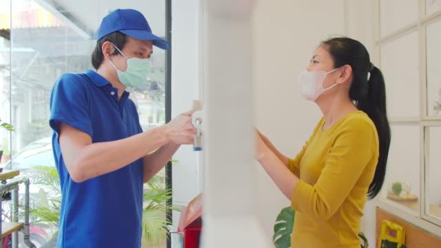 stockvideo's en b-roll-footage met aziatische mannelijke arbeider die van de leveringsdienst het pakket aan een vrouw in quarantaine, het sociale distantiëren en sluit concept af. - vermijden