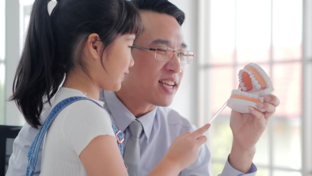 asian male dentist talking to brush teeth properly explained to the girl were listening to in the hospital.medical system in china & hong kong - toothbrush stock videos and b-roll footage