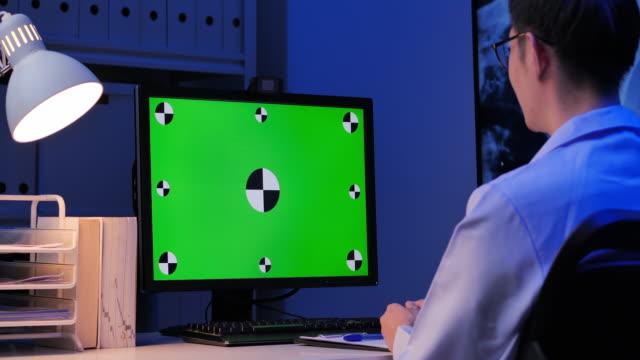 vidéos et rushes de médecin masculin asiatique regarde l'écran vert à la vidéoconférence pendant l'emplacement à distance par ordinateur à la maison la nuit de travail tard. écran vert à la maison - remote location