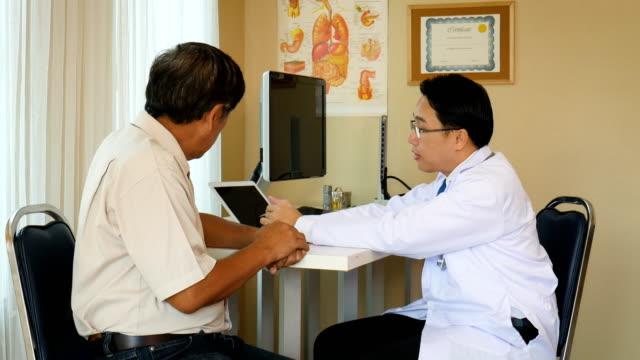 アジアの男性医師が病室で年配の患者男性とデジタル タブレットの議論を使用して - 説明する点の映像素材/bロール