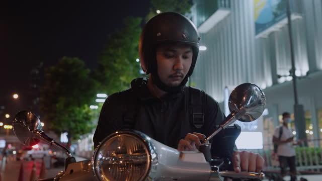asiatische männliche lebensmittelkurier auf der suche nach der lieferadresse - motorroller stock-videos und b-roll-filmmaterial