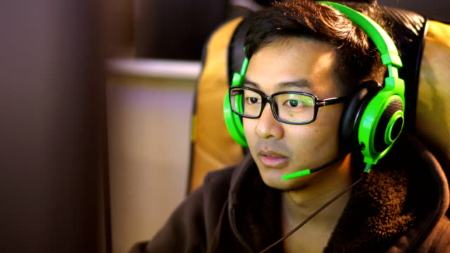 CU Asian male gamer playing game in green headset with microphone
