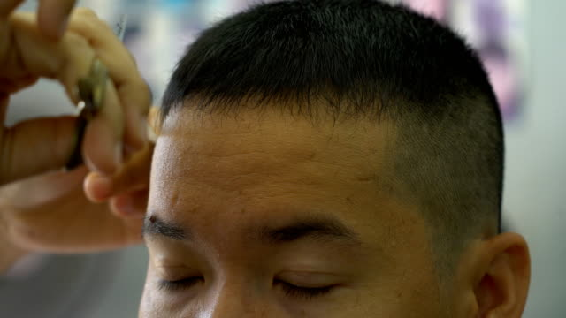 asian male getting haircut by barber while sitting in chair at barbershop - barber chair stock videos & royalty-free footage