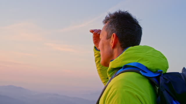 slo mo asian male hiker observing the surrounding mountains from the mountain top at sunset - 45 49 years stock videos & royalty-free footage