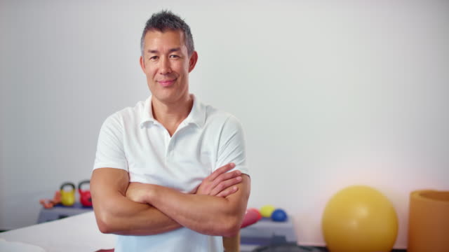 slo mo asian male physical therapist smiling into the camera - physiotherapy stock videos & royalty-free footage