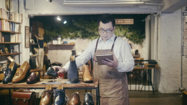 asian male shoe shop worker arranging display in menswear shoe shop - department store stock videos & royalty-free footage