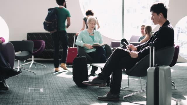 vídeos de stock, filmes e b-roll de asian male waiting in airport lounge on mobile phone - área de embarque de aeroporto