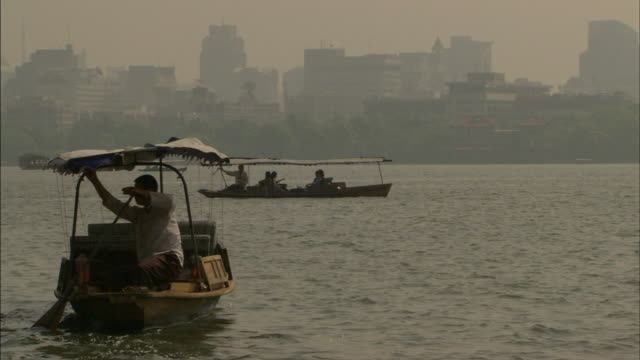 asian male working oar on stern of canvas roof tourist boat, sculling, moving out of frame, open sight-seeing boats bg, cityscape in hazy fog.... - sculling stock videos & royalty-free footage