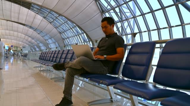 asiatischen männlichen arbeiten mit laptop während des wartens flug am internationalen flughafen - wartehalle stock-videos und b-roll-filmmaterial