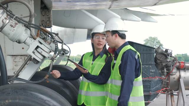 asiatische mann und frau ingenieur wartung flugzeug team reparaturen, reparaturen, modernisierung und renovierung vor dem flugzeug vom flughafen. - luftfahrzeug stock-videos und b-roll-filmmaterial