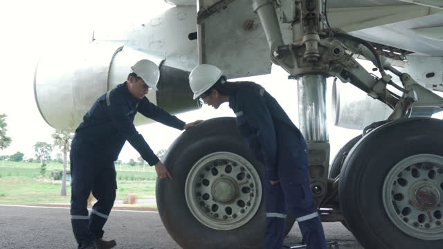 asian man and woman engineer maintenance airplane team repairs, fixes, modernization and renovation in front airplane from  in airport. - air vehicle stock videos & royalty-free footage