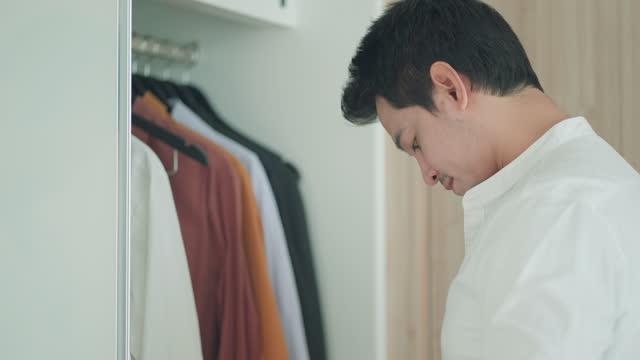 アジア人男性は、自宅の楽屋で午前中に仕事に行く準備をして、服を着るためにシャツをボタンで留めます。 - all shirts点の映像素材/bロール