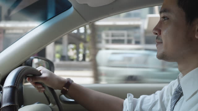 asian man are driving on city streets to get to work in the morning. - only men stock videos & royalty-free footage