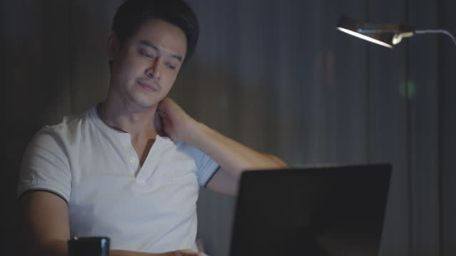 asian man are stretch lazily while working long hours in front of a computer in late night in living room at home. - neck stock videos & royalty-free footage