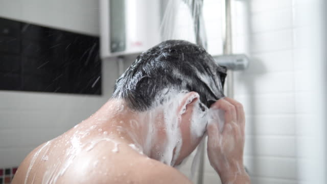 asian man are taking hair and body wash shower in bathroom. - shower stock videos & royalty-free footage