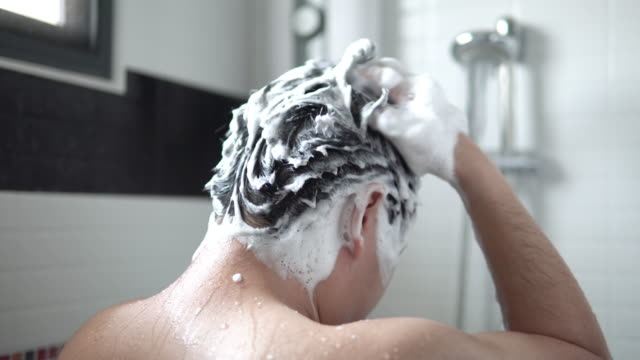 asian man are taking hair and body wash shower in bathroom. - shampoo per capelli video stock e b–roll