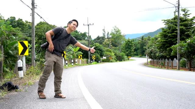 vídeos de stock, filmes e b-roll de homem asiático pedindo carona em área rural - perguntando
