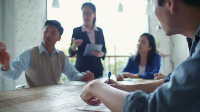 asian man attending professional training session led by businesswoman - leadership training stock videos & royalty-free footage